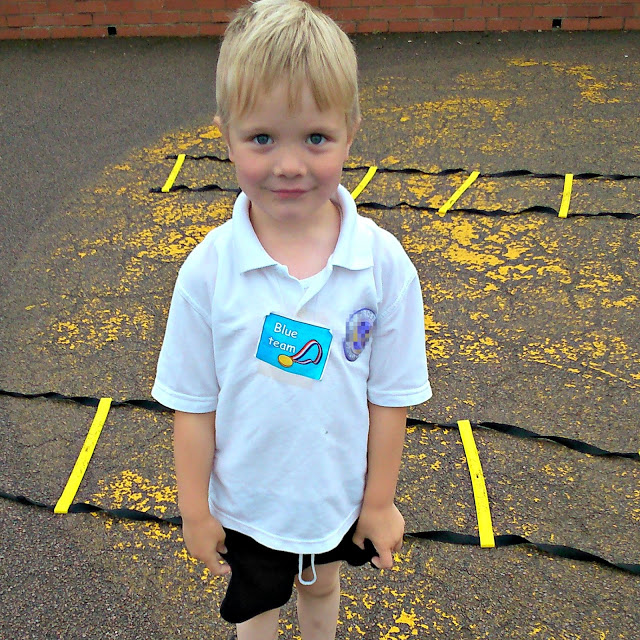 little man in p.e. kit in playground.