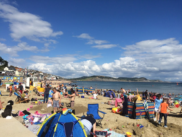 The beach full of holiday makers, the sea and a lovely blue summer sky