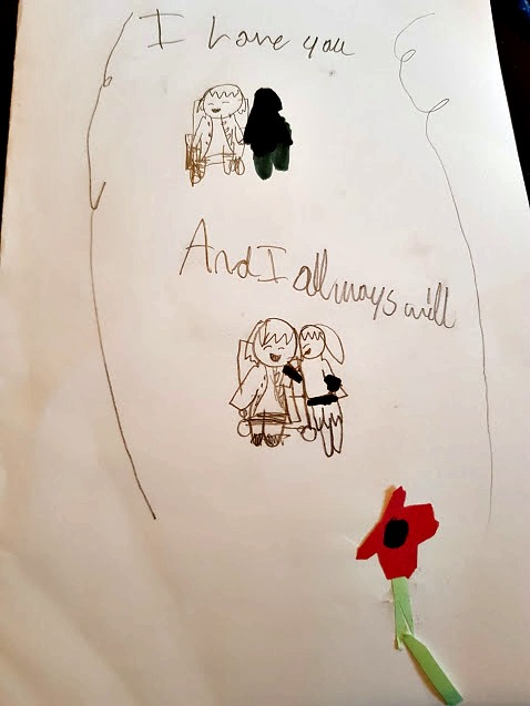 mothers day card drawn by Boo, it shows me in my wheelchair with her at my side and a little red flower. It says, I love you and I always will.