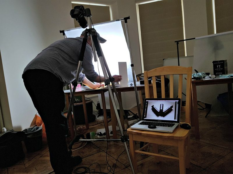 a photographer setting up a light environment for taking product photography, at the front there is a chair with a laptop on to view the photos.