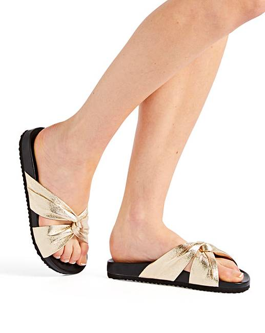 flat sandals with gold fabric knots.