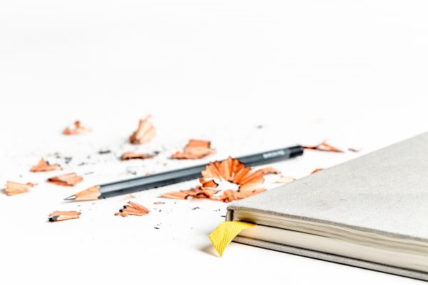 a school book sitting alongside a pencil and pencil sharpenings