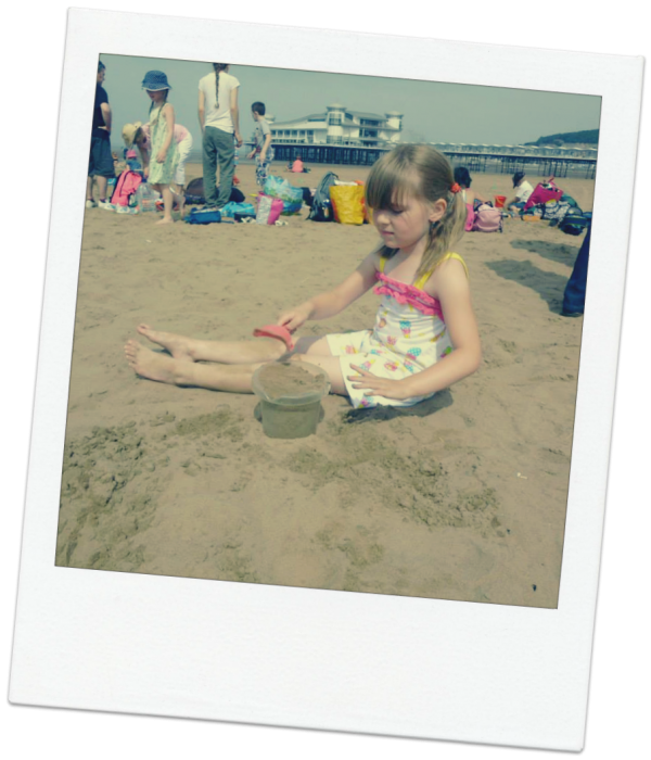 little girl on the beach in 2013 playing in the sand.