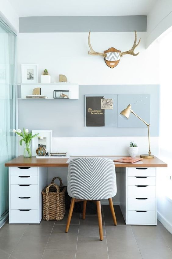 two white cabinets with a plank of wood across the top to make a desk
