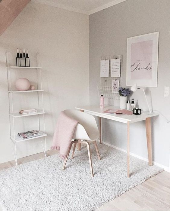 a simple white desk and matching chair against a grey painted wall with a wire bookcase